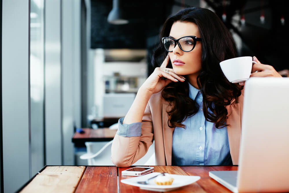 Thoughtful young woman with glasses and dark hair holding a cup of coffee