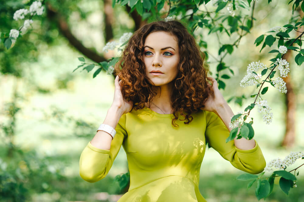 Beautiful curly-haired woman in elegant green dress in the garden
