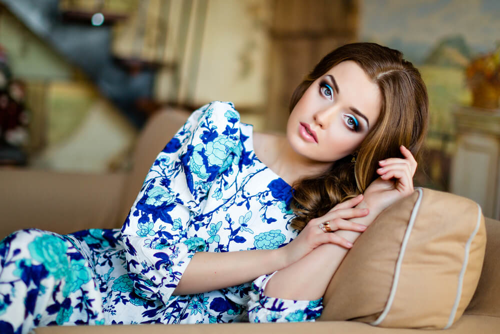 Beautiful woman in blue floral dress resting on the sofa